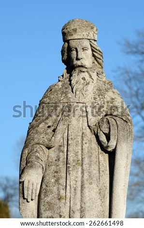 The old stone statue of saint on gravestone in Ukraine - stock photo