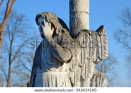 The old stone statue sad angel headstone in the cemetery - stock photo