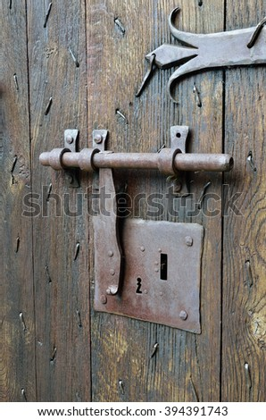 The Old Style Big Metal Lock With A Latch On The Wooden Surface Of The