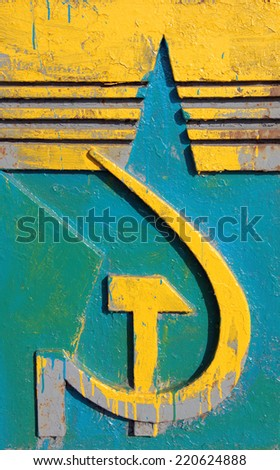 The old symbols of the Soviet Union star, hammer and sickle painted in national colors of Ukraine - stock photo