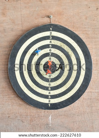 The old target with darts in the center on the wood wall