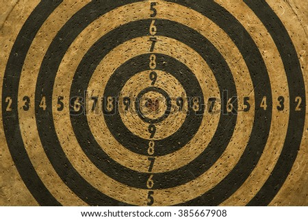 The old target with darts in the center on the wood wall  - stock photo