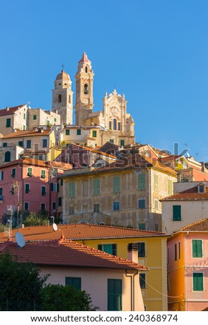 The old town of Cervo, Liguria, Italy, with the beautiful baroque church arising from the houses. Clear blue sky. - stock photo