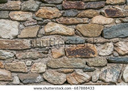 The old wall of grey and brown stones