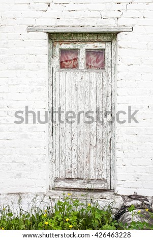 The old white painted door against a white brick wall - stock photo