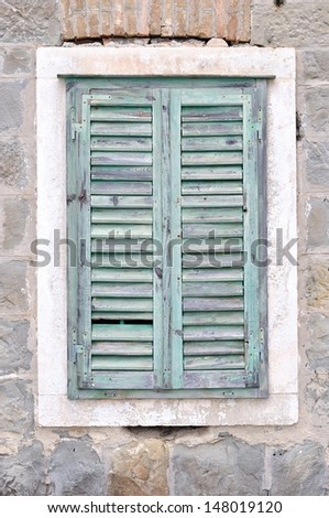 The old window with blue closed shutters on an old house. Vintage background, texture. - stock photo