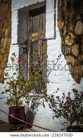 The old window with closed shutters on a white wall - stock photo