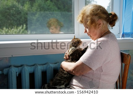 The old woman holds cat in a lap - stock photo