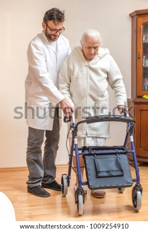 The old woman in a white bathrobe walks with the help of a walker with the assistance of a nurse.