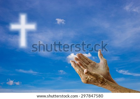 The old woman's hands praying over blurred the cross on the sky background.