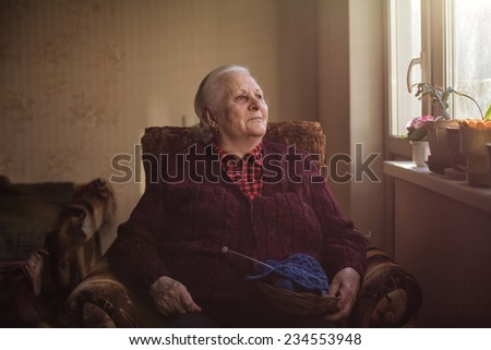 The old woman sits at home and knits garments. - stock photo