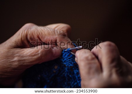 The old woman sits at home and knits garments. Close up.