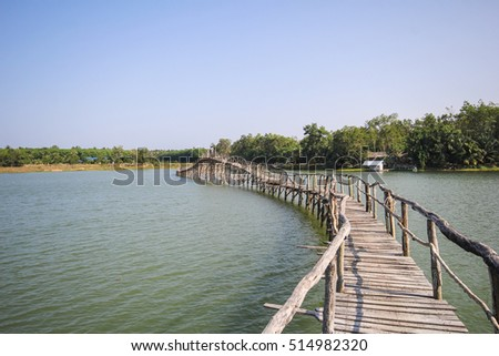 The old wood bridge in lake of Chumphon Thailand