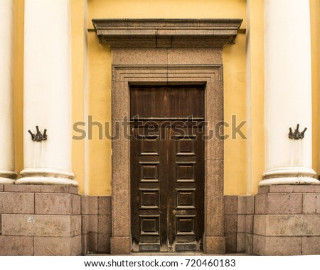 The old wooden door, brown in the middle white columns