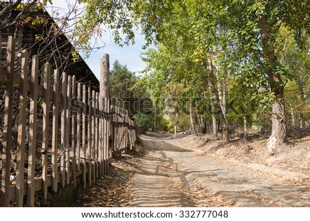 the old wooden fence constructed along the road to stables - stock photo