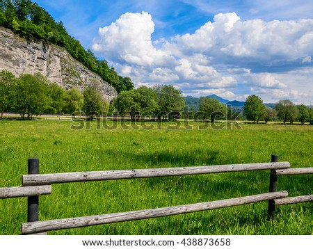 The old wooden fence surrounding natural green Alpine meadow with snowy mountain peaks under a beautiful feather clouds on a bright blue sky in the background, Salzburg, Austria - stock photo
