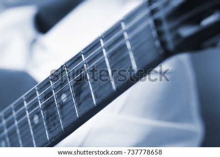 the old wooden guitar fretboard with strings and frets