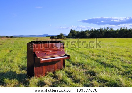 The old wooden piano outdoors. - stock photo