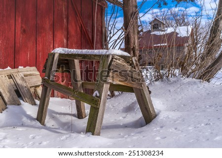 The old wooden saw horse in the snow on a country farm scene.  - stock photo
