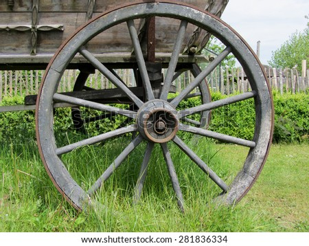 The old wooden wheel on a hay. - stock photo