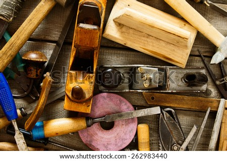 The old working tool. Many old working tools (axe, drill, saw and others) on a wooden background. - stock photo