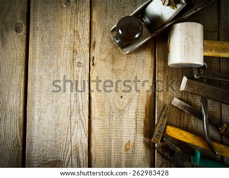 The old working tool. Many old working tools ( hammer, pliers, plane and others) on a wooden background. - stock photo