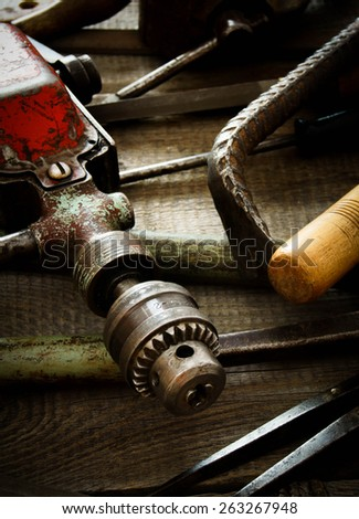The old working tool. Many old working tools ( mount, drill, corner and others) on a wooden background.