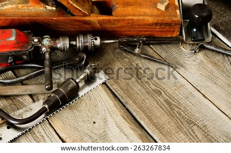 The old working tool. Many old working tools (plane, drill, mallet and others) on a wooden background. - stock photo