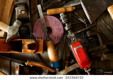 The old working tool. Many old working tools ( ruler, drill, chisel and others) on a wooden background. - stock photo