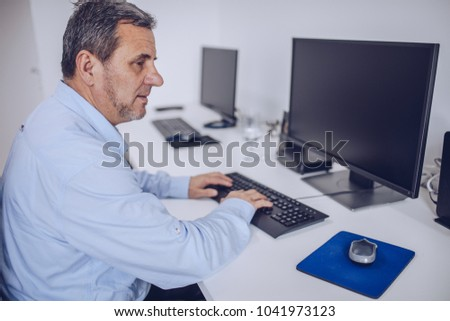 The older man works on the computer