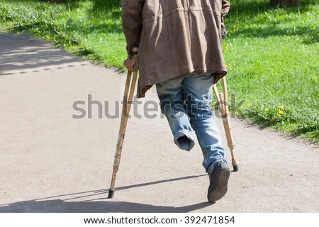 the one-legged disabled person walks in park on crutches in clear summer day - stock photo
