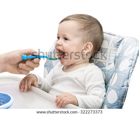 The one-year-old kid eats porridge isolated on the white