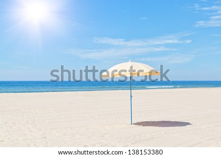 The only beach umbrella on the sea in summer under the sun. - stock photo