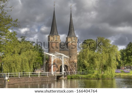 The Oostpoort gate in sunlight and dark rainclouds above in Delft, Holland - stock photo