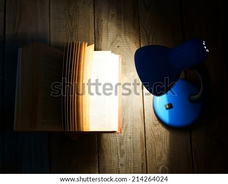 The open book and the fixture. On a wooden background. - stock photo
