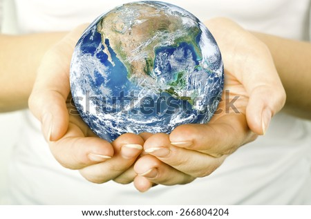 The open hands of woman and earth in. Elements of this image furnished by NASA - stock photo