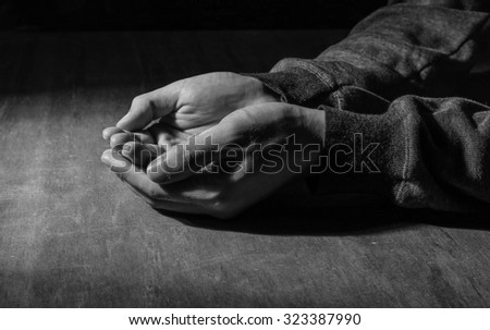 The open praying hands on the wooden desk background. - stock photo