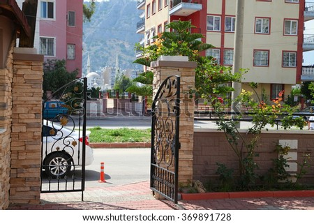 The openwork forged gate in the city yard