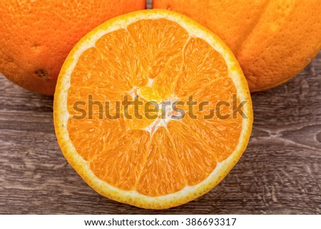 The orange oranges on a brown wooden background
