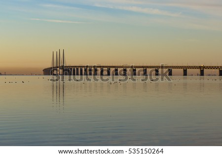 The Oresund bridge between Copenhagen Denmark and Malmo Sweden, when sunset in December and silent sea. Copenhagen in the background on the other side of Oresund