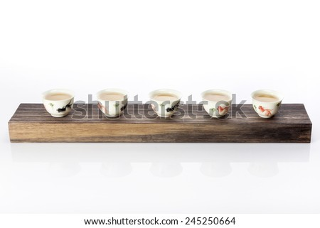 The oriental(chinese) tea cup with tea, wood block isolated white at the studio. - stock photo