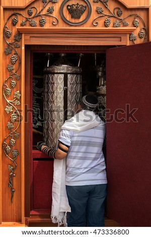 The orthodox Jew gets  Sefer Torah  (old testament)  in  silver fancy containers  from  cabinet near a Western Wall, Jerusalem, Israel