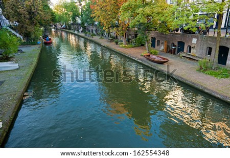 The Oudegracht (old canal) that runs through the center of Utrecht, with the Dom tower in the background. - stock photo