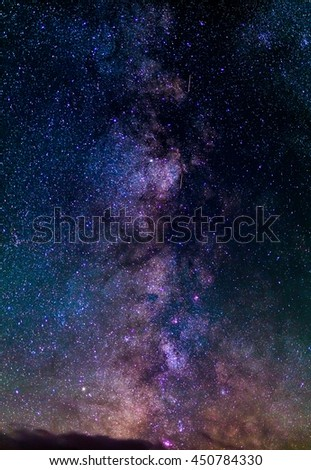 The outstanding beauty and clarity of the Milky Way, with details of its colorful core. Vertical panorama of 6 stitched photos. Telephoto captured high up from the Alps. - stock photo