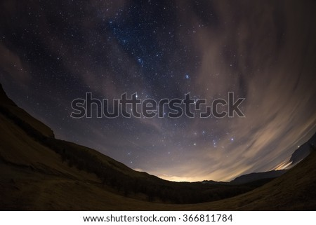 The outstanding beauty of the starry sky and Milky Way in winter season, captured by fisheye lens with scenic distortion and 180 degree view. Some digital noise due to 1600 iso setting. - stock photo
