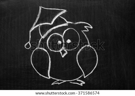 The owl in the hat on an old , scratched the chalkboard . - stock photo
