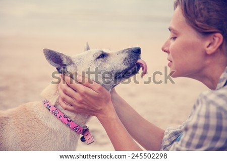 The owner with her dog on the beach. Best friends, - stock photo