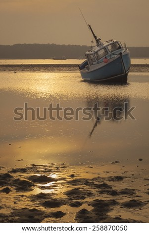 The pace of the receding tide has caught out this fisherman whose ship is grounded under the setting sun - stock photo