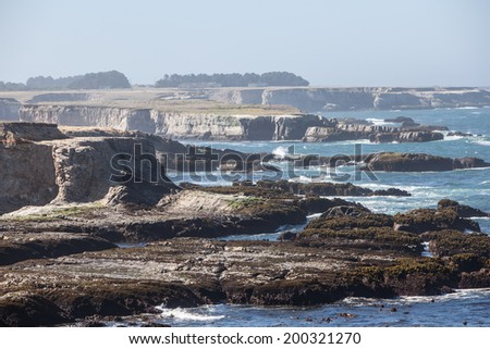 The Pacific Ocean has worn Northern California's coastline into dramatic scenery. The eroded shoreline forms scenic, craggy coves that can be viewed from the Pacific Coast highway. - stock photo