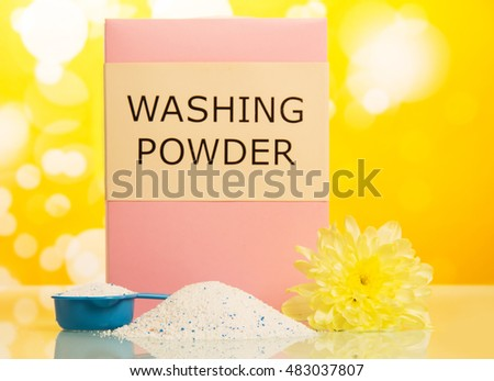 The pack of washing powder in a measuring cup on abstract yellow background.